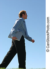 Business strut - Business man in blue shirt is walking in a...