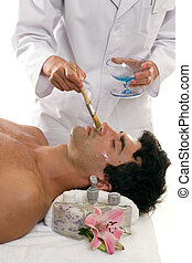 Skincare - A woman applies a purifying mask to a male...