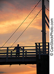 Man watching sunset on a footbridge in Perkins Cove, Maine