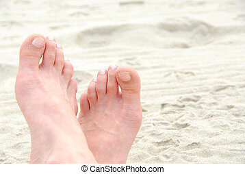 Sandy feet - Crossed sandy feet on a beach