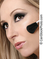 Woman\\\'s face and makeup brush - Closeup of a female using...