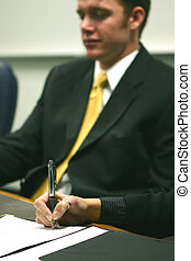 Signing the contract - Business man dressed in gray suit is...