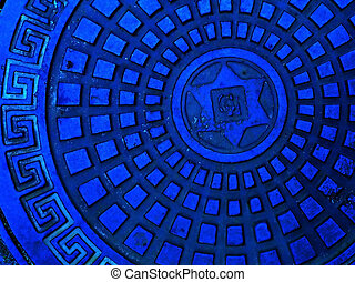 Sewer cap in blue color with meander pattern as a background