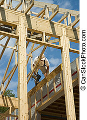 Framing a house 1 - Construction worker framing the roof of...