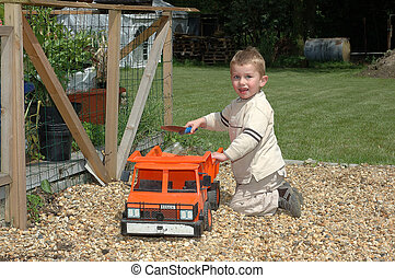 Child playing in garden. - Toddler playing with toy in...