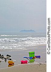 Beach toys - Bright colored beach toys on a deserted beach