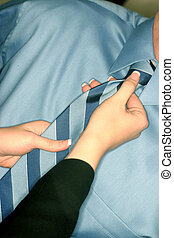 Woman adjusts boss tie - Business woman adjusts the blue tie...