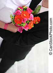 Bride and groom are holding each other with a bouquet of...