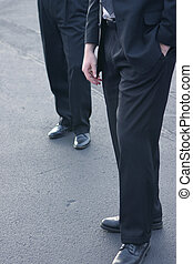 Businessmen standing - Two business men dressed in dark...