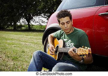 playing guitar10 - cool guy playing guitar besides his car
