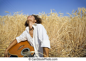 playing guitar11 - cool guy laying in a cornfield playing...