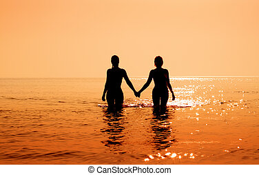tropical sunrise - silhouette image of two bikini girls...