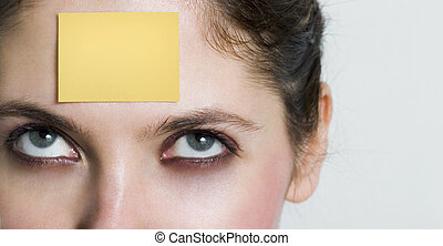 post-it - girl looking up to a yellow post it sticked on her...