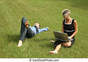 Business Team - Business woman working in the grass while...