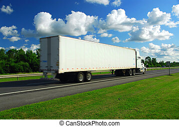 Fast moving truck with white container on highway, blurred...