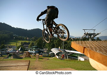 downhill - mountainbikerider on northshore ramp in...