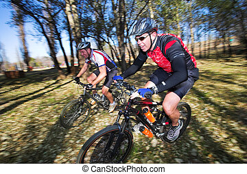 Mountainbiking #3 - Panning shot of two mountain bikers,...
