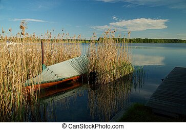 Wooden boat in reeds - Sky is mirroring in the water and a...