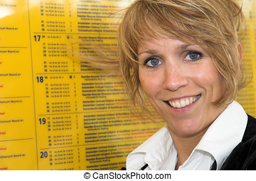 Checking the train schedule - Businesswoman checking the...
