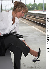 Sore feet - Pretty businesswoman rubbing her feet which hurt...