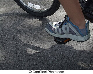 Foot on a pedal - foot in a running shoe on a bicycle pedal