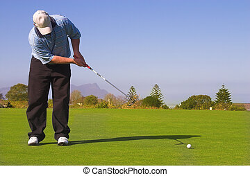 Golfer putting on the green. Golf ball in motion. Copy...