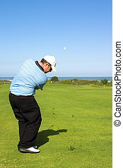 Golfer hitting the ball to the green. Ball in motion in the...
