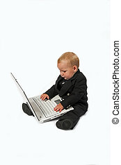baby computing - Young child in suit working on a laptop...