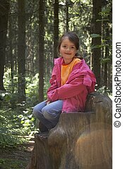 girl sitting on a tree stump 01 - girls playing on a tree...