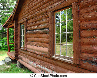 Reflections - the windows of a log cabin reflecting the...