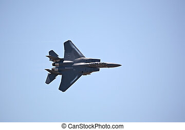 F-15 strike eagle in flight against blue sky, banking hard...