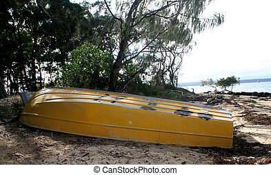 Yellow Dinghy - A yellow dinghy lying on a deserted beach in...