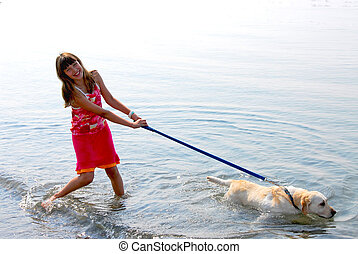 Girl playing dog - Happy girl playing with her dog in water
