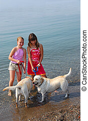 Two girls playing with dogs