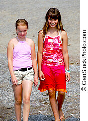 Two girls walking - Two preteen girls walking on a beach