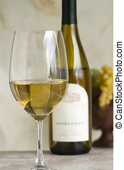 chardonnay - glass of chardonnay with bottle and grapes in...