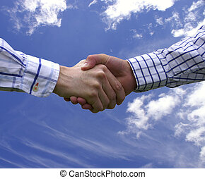 Handshake with sky and clouds in background.