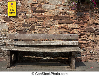 empty bench with a sign stating no parking at any time on...