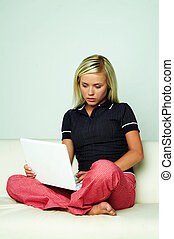 Using laptop - Young pretty women on white couch relaxing...