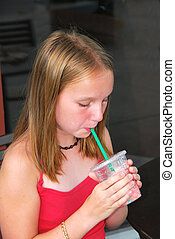 Girl with a drink - Young girl sitting in outside cafe and...