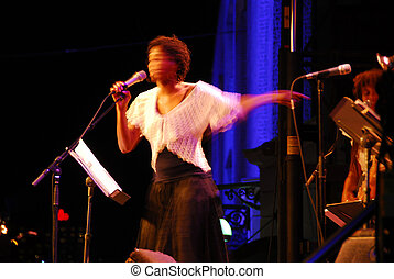 Jazz singer on outdoor stage, image is blurred by long...