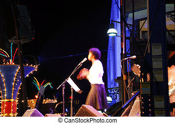 Jazz singer on outdoor stage clapping hand, motion blur my...