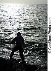 fisher man standing on rocks & waves of sea