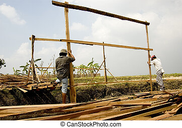 Makeshift Builders - Men building temporary shelter on a...