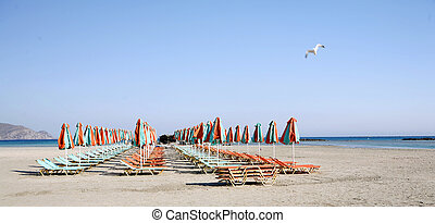 Beach umbrellas and sunbeds at Elafonissos, Crete there is...