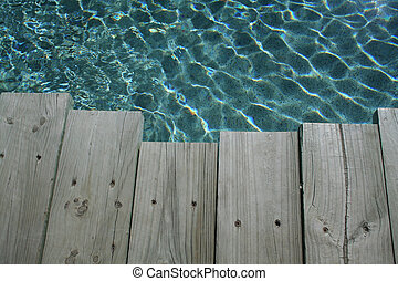 Wood by Pool - Wooden planking beside a swimming pool on a...