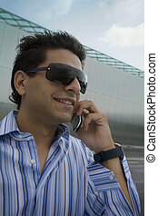 mobile phone - young businessman talking on the phone in his...