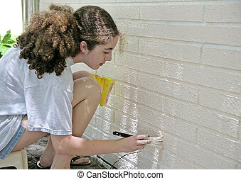 Teen Painting House Trim - A teen girl painting house trim....