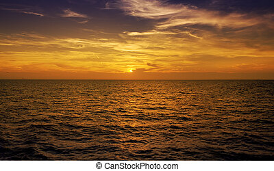 big calm - warm sunset on open ocean. The focus is on the...