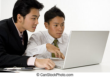 Computer Work - Two young asian men working on a laptop...